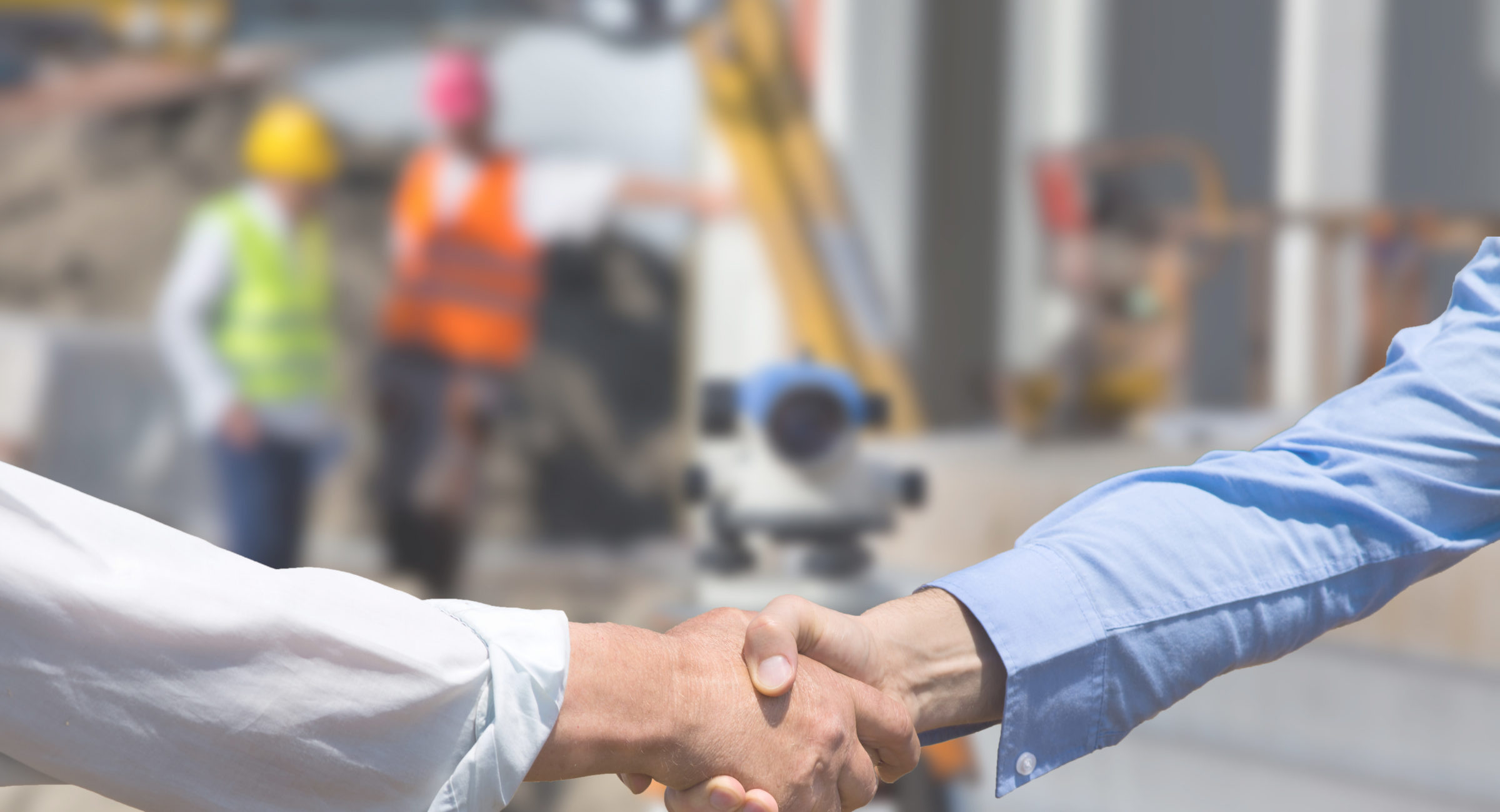 Two business people shaking hands in front of leveling instrument on construction site with workers in background